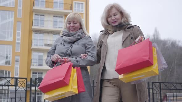 Thumbnail for Senior Caucasian Women Strolling on City Street After Shopping. Happy Active Middle-aged Retirees