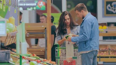 Beautiful Girl with a Guy Buying Vegetables in a Store