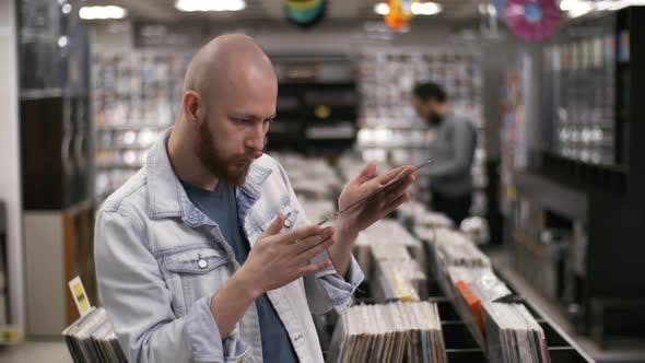 Thumbnail for Avid Music Collector Checking Rare Vinyl Disc in Record Shop