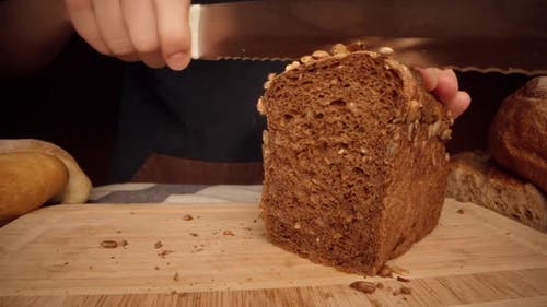 Hands of a Woman Cutting Bread Loaf on Wooden Cutting Board