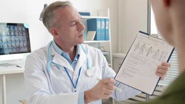 Physician Filling in Patient Card