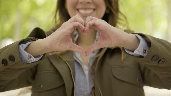Thumbnail for Smiling Woman Making Heart Shape with Hands