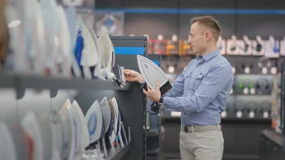 Thumbnail for A Young Handsome Man in a Shirt Chooses an Iron in a Consumer Electronics Store. Bachelor