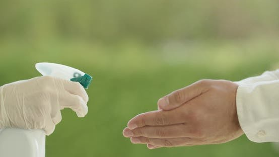 Disinfecting Hands With Spray