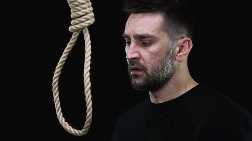 Verängstigter verzweifelter Mann legt Hangmans-Schlinge um den Hals, Selbstmordversuch
