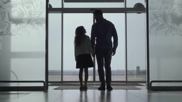 Thumbnail for Back View Silhouettes of Adult Man and Little Girl Standing at the Airport Door and Looking at the