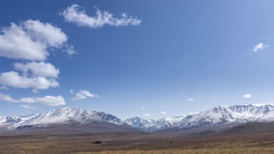Thumbnail for Timelapse of Sun Movement on Crystal Clear Sky with Clouds Over Snow Mountain Top. Yellow Grass at