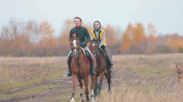 Two Women Are Galloping on the Bay and Beautiful Horses