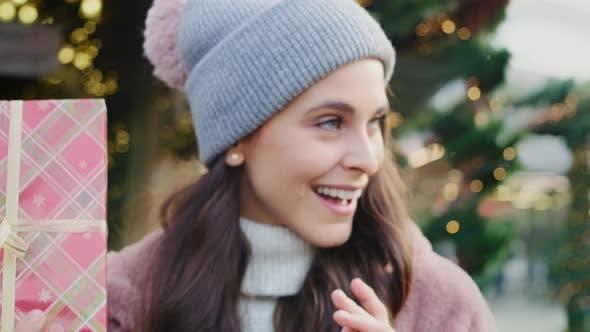 Thumbnail for Handheld-Ansicht der schönen Frau schütteln Weihnachtsgeschenk
