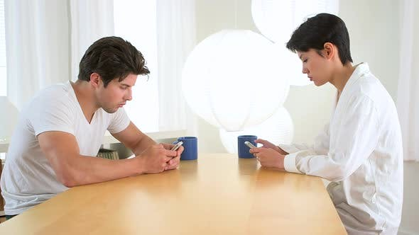 interracial paar SMS auf Ihre Telefone bei Tisch