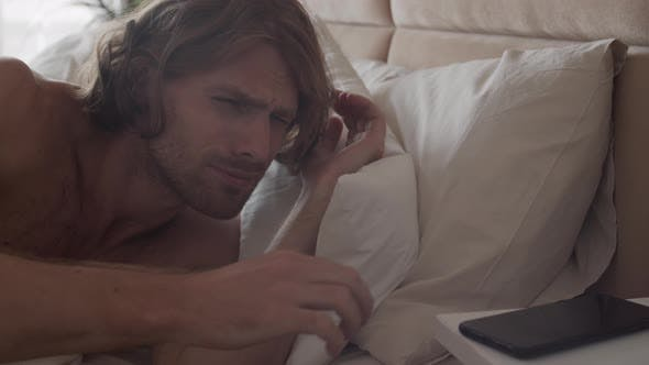 Man Waking Up and Checking Time