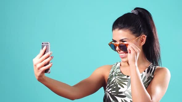 Thumbnail for Confident Young Cheerful Girl with Straight Black Hair, Poses on a Blue Background with Smartphone