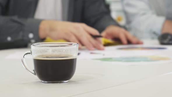 Thumbnail for Close Up of a Cup of Coffee on the Table Businesspeople Working on the Background