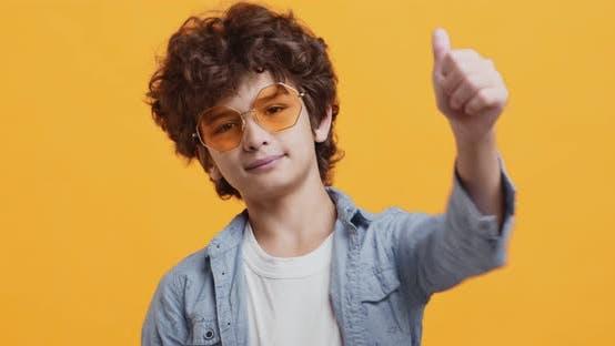 Awesome Curly Boy zeigt wie Geste, Lächeln in Sonnenbrillen und Jeansmantel
