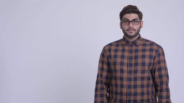 Happy Young Bearded Indian Hipster Man Showing Something