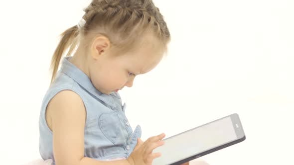 Thumbnail for Baby Is Holding a Computer in Her Hands and Cliches, She Is in a Good Mood. White Background