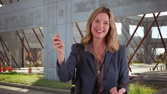 Thumbnail for Smiling portrait of real estate agent holding keys outside