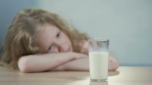 Thumbnail for Sad Female Kid Sitting at The Table and Looking at Glass of Milk, Breakfast