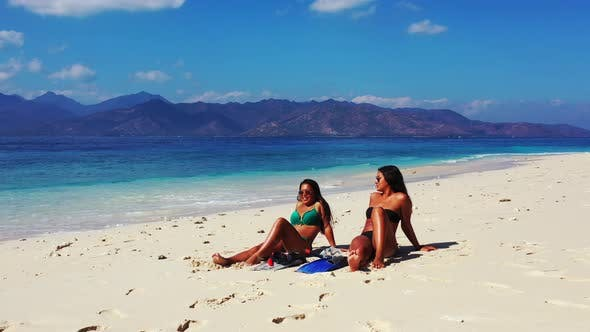Thumbnail for Young smiling ladies on vacation having fun at the beach on clean white sand and blue 4K background