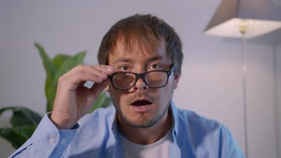 A Man in Surprise Shoots Glasses and Looks at the Camera in Surprise. Businessman Shocked.