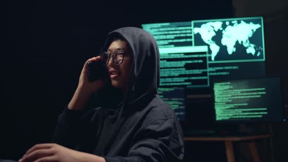 Asian Boy Hacker Using Computer Hacking And Talking On Phone
