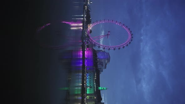 Vertical video of The London Eye and Thames River at night, an iconic London building and famous tou