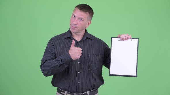 Thumbnail for Macho Mature Businessman Showing Clipboard and Giving Thumbs Up