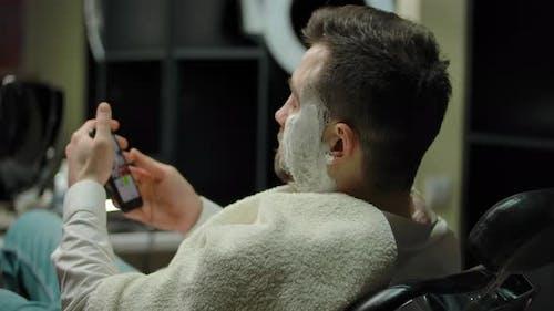 Handsome Guy Indoor of Barbershop Scrolling Socials