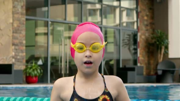 Cheerful Girl in Goggles Bathing in the Pool