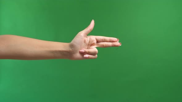Woman's Hand Making Shooting Gun, Hand Pistol Gesture On Isolated On Green Screen Background