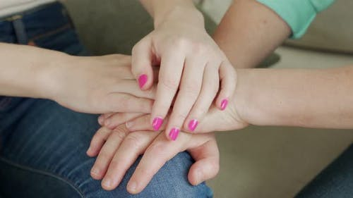 Close Up of Female Young Hands Holding an Elderly Woman's Hands