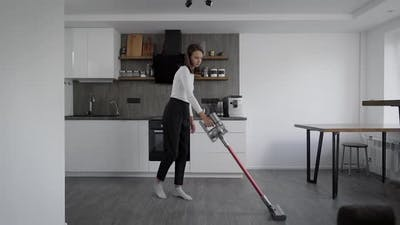 Cleaning in a Stylish Kitchen. A Girl Vacuums the Floor.