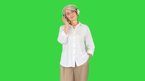 Calm Senior Woman Listening Music with Headphones on a Green Screen Chroma Key