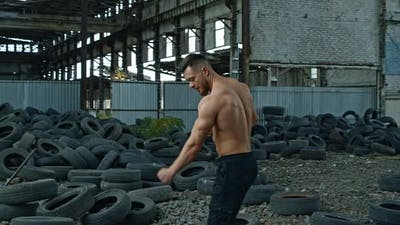 Shirtless bodybuilder in abandoned place