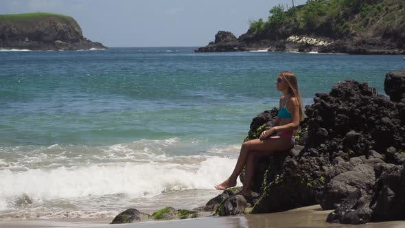Thumbnail for Girl Sits on the Rock and Looks at the Sea. Bali, Indonesia