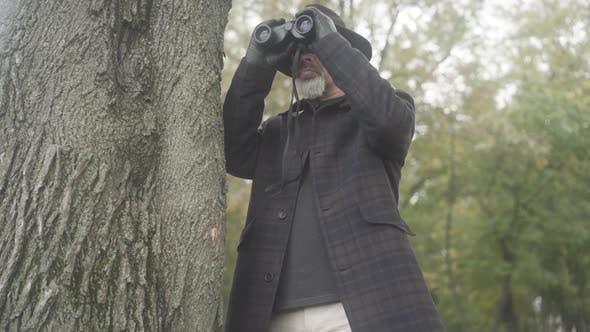 Thumbnail for Mittlerer Schuss eines konzentrierten seriösen Detektivs oder Geheimdienstmitwirkers mit Ferngläsern zum Spionieren