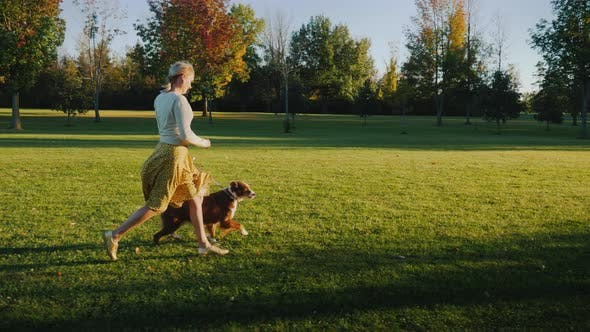 Thumbnail for Active Woman Runs with the Dog in the Park