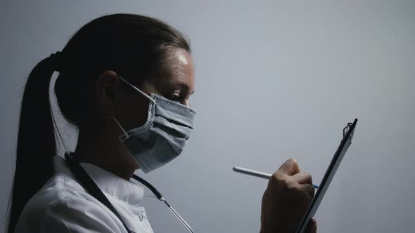 Physician makes notes on a patient's medical record
