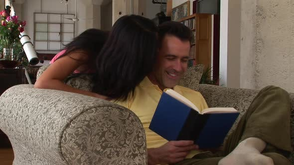 Thumbnail for Romantic young couple reading a book and kissing