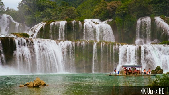 4K Panoramic Ban Gioc Waterfall In Vietnam With Boat of Tourists