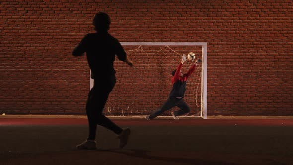 Thumbnail for Two Young Men Friends Playing Football on the Outdoor Playground at Night - Protecting the Football