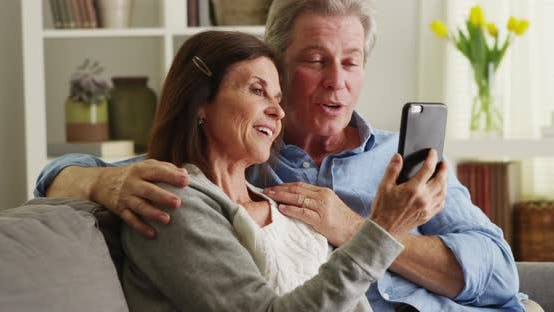 Thumbnail for Happy senior couple using smartphone on couch
