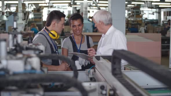 Thumbnail for Elderly Manager Discussing Machinery with Factory Workers