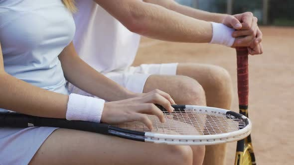 Thumbnail for Nervous couple of tennis players sitting on bench and waiting for match results