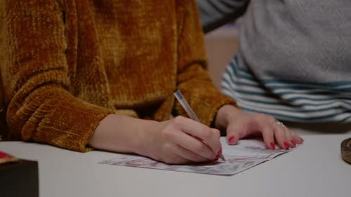 Close Up of Woman Holding Pen and Signing Christmas Card