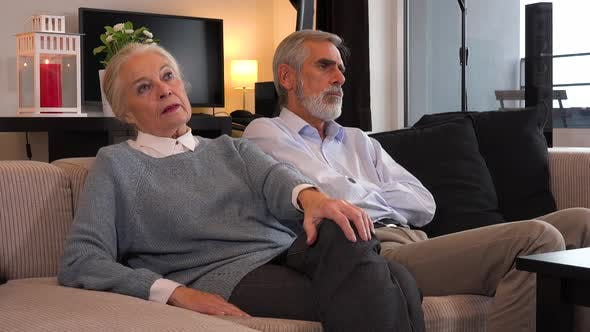An Elderly Couple Sits on A Couch in An Apartment, the Man and ...