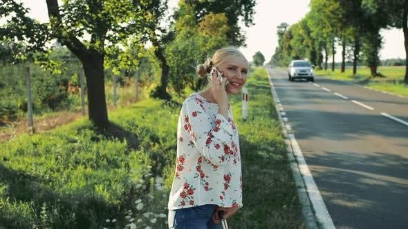 Girl Speaking on Phone While Hitchhiking