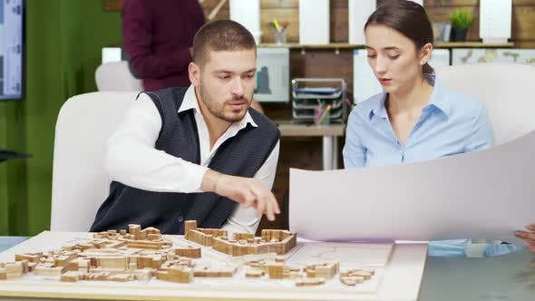 Team of Architect Holding Blue Print and Working with Building Models