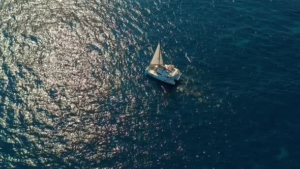 Thumbnail for Aerial View. Catamaran Goes By Sea, Camera Move Closer and Fly Over Vessel, on the Sunset, Beautiful
