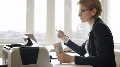 Business Woman Counting Cash in Counting Machine Sitting at Wooden Desk and Counting Large Bundle of